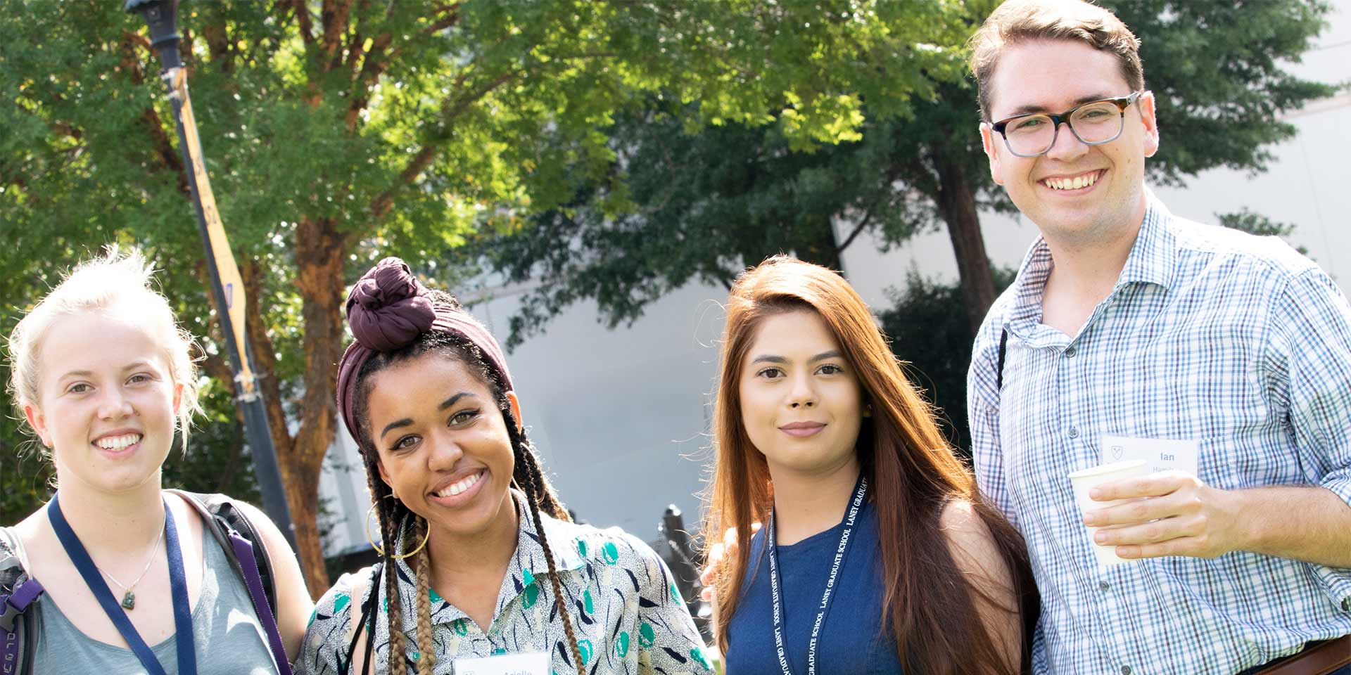 A diverse group of four students pose and smile during new student orientation.